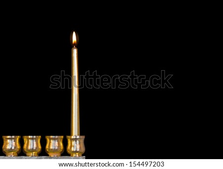 One Jewish holiday Chanukah candle. Bright, shiny yellow candle glowing for the first night. Gold color menorah cups. Room for text, copy space. Isolated on a black background. Horizontal. Copy space. - stock photo