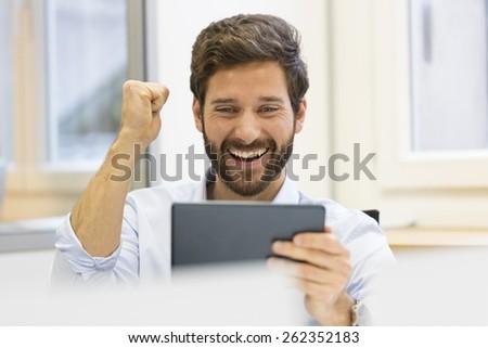 One joyful man holding digital tablet - stock photo