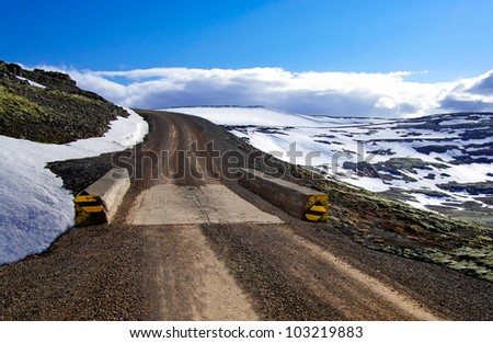 One Lane Bridge:  A narrow bridge allows passage of only one vehicle at a time on a gravel road in the mountains of Iceland. - stock photo