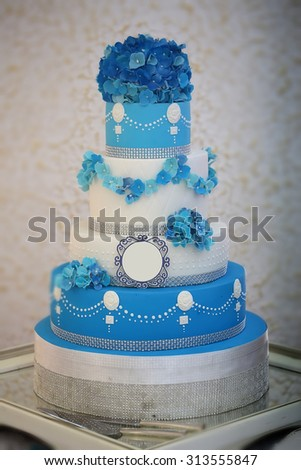 One large beautiful delicious many-tier decorated wedding cake white and blue colours with flower garlad and hydrangea bouquet on top, vertical picture - stock photo