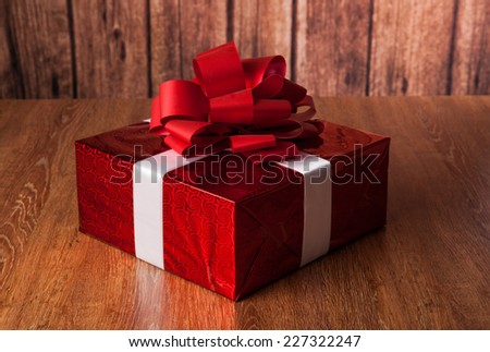 one large red gift box on a wood background - stock photo