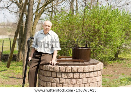 One legged man sitting on an old well in a rural park looking at the camera holding his crutches in one hand - stock photo