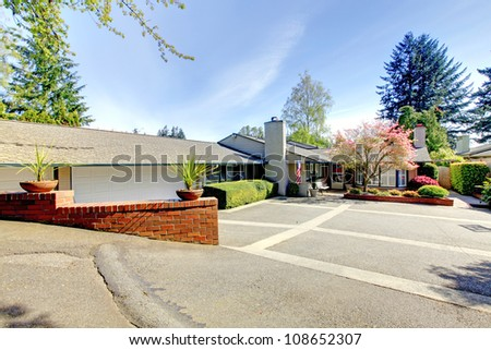 One level American house with large parking area and spring landscape. - stock photo
