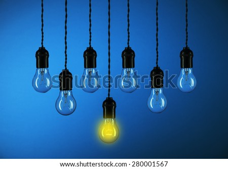 One light bulbs with glowing one isolated over blue background-leadership concept - stock photo