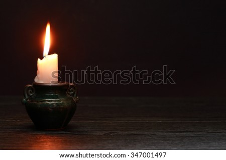 One lighting candle in candlestick on dark background - stock photo