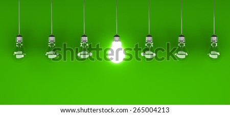 One lit lightbulb, on green background with other unlit ones.  - stock photo