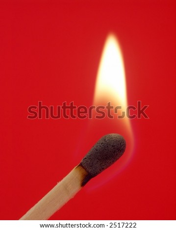 One lit wooden matchstick isolated on red background. - stock photo