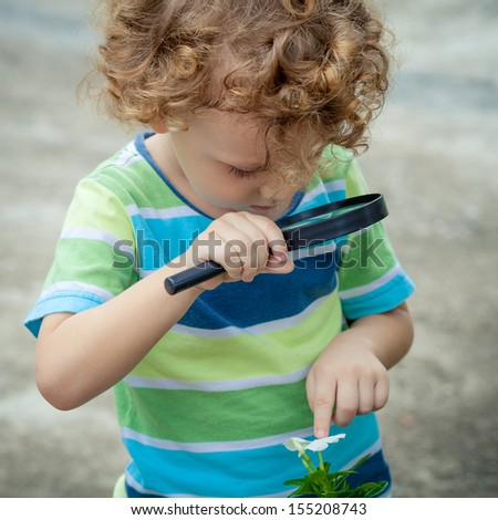 one little boy with magnifying glass outdoors in the day time - stock photo