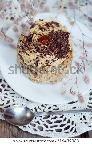 One little cake with cream, jam and chocolate sprinkles for dessert - stock photo