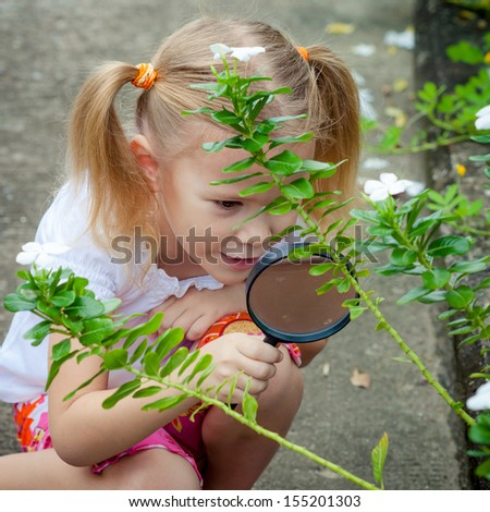 one little girl with magnifying glass outdoors in the day time - stock photo
