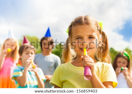 One little 5 years old beautiful girl blow noisemaker on a birthday party wearing cap with friends standing on background - stock photo