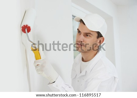 One male house painter worker painting and priming wall with painting roller - stock photo