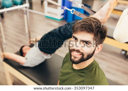 One man exercising on a reformer bed and another taking a picture - stock photo