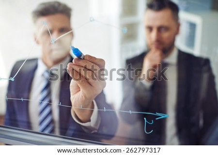One man explaining graph to another person - stock photo