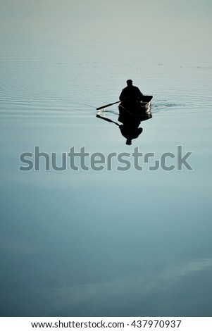 one man in a small boat sailing boat on the lake river rowing oars. River with a smooth mirror surface of the water. Weather quiet, calm, windless - stock photo