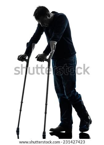 one man injured man walking sad with crutches in silhouette studio on white background - stock photo