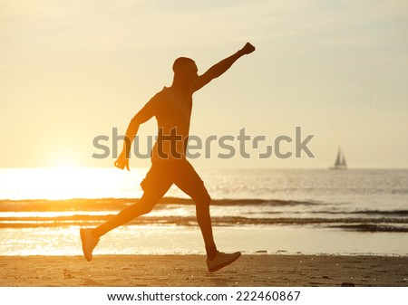 One man running on beach with hand raised and sunset in background - stock photo