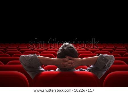 one man sitting in empty cinema or theater auditorium - stock photo