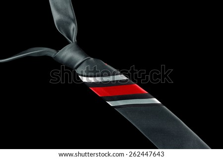 One necktie isolated against a black background. White, black and red stripes. - stock photo