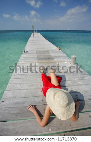 One of a large series. Woman in red bikini sunbathing on a tropical jetty - stock photo