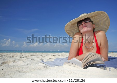 One of a long series of photos taken on the Mexican Caribbean coast. Woman reading on the beach with a big hat - stock photo