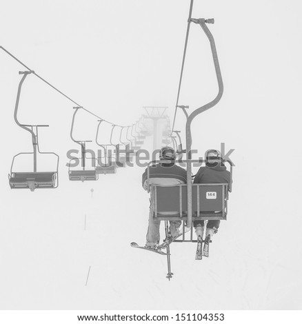 One of chair lifts in a ski resort of a valley of Zillertal in the fog - Mayrhofen region, Austria (black and white) - stock photo
