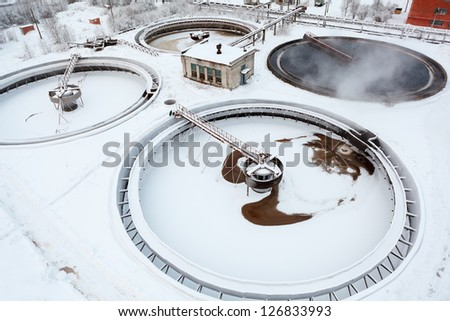 One of four working round settler on sewage treatment plant in winter season - stock photo