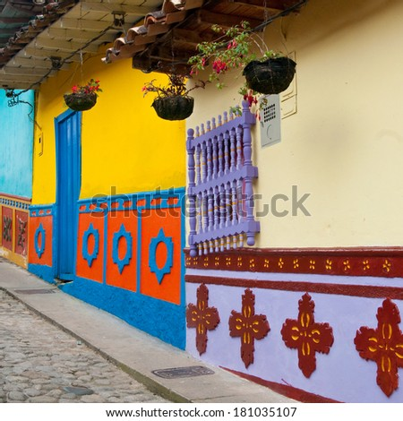 One of many colorful streets in Guatape, Colombia (square, 1x1) Every building/house has tiles along the facade's lower walls in bright colors and dimensioned images. - stock photo