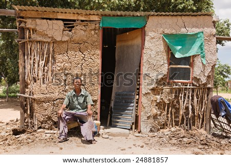 One of the few remaining bushman sitting down in front of his traditional shack, the indigenous people of Kalahari. - stock photo