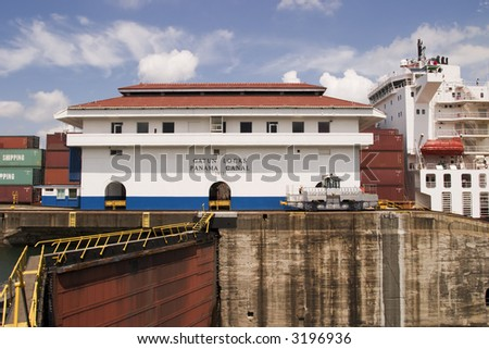 One of the main buildings at Gatun Locks in the Panama Canal with a large container ship full of cargo in the background. - stock photo