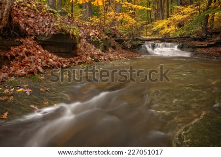 One of the many scenic waterfalls along the Sulpher Springs Creek in Ohio during peak fall colors. This small waterfall looks it's best with peak autumn colors in the trees.  - stock photo