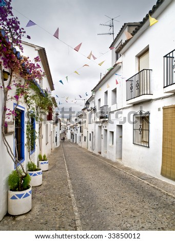 One of the streets of the beautiful old town of Altea, located in the Costa Blanca of Spain. White houses with flowers on the walls and small paper flags in the sky heralding the festival of the town - stock photo