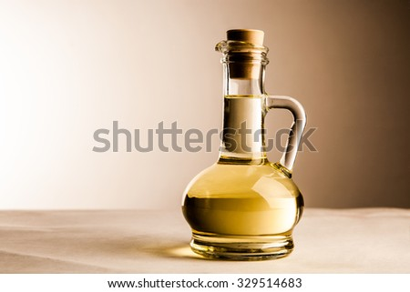 one Olive oil in transparent glass bottle on white or gray wall background Empty space for inscription or other objects  - stock photo