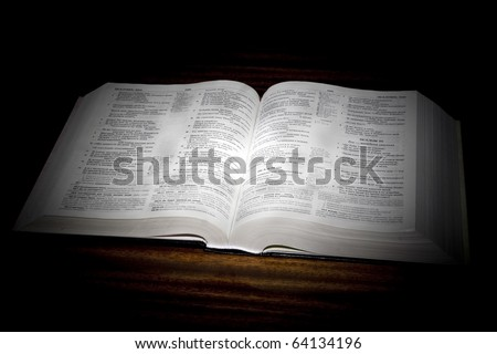 One open bible on table in black background - stock photo
