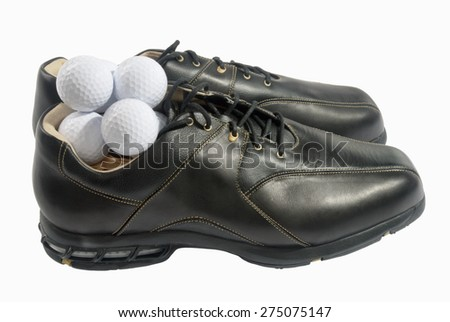 one pair of new clean black mens golf shoes with a pile of white golf balls inside one shoe. This is a side view shot so the upper part of both shoes can be seen. The background is isolated on white.  - stock photo