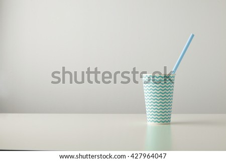 one paper cup decorated with blue line pattern and with blue drinking straw inside isolated on white table Place for your text above - stock photo