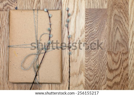 One parcel or box in eco paper on the wooden table. Top view. Gift box tied with twine. Willow branch with a parcel. - stock photo