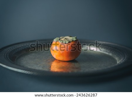 One persimmon on a silver platter against a gray background.  - stock photo