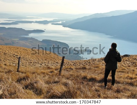 One person standing on Ben Lomond looking at a panoramic view of Loch Lomond - stock photo