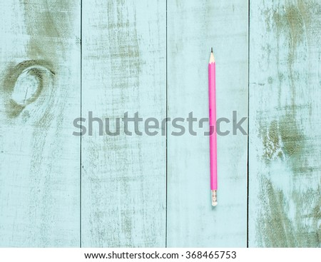 One pink pencil on blue wooden background. - stock photo