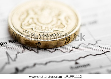 One pound coin on fluctuating graph. Rate of the pound sterling - stock photo