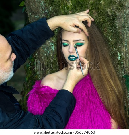 One pretty fashionable young woman with long hair and emerald bright makeup in purple fur waist coat and professional visagiste near tree trunk with moss in evening forest outdoor, square picture - stock photo