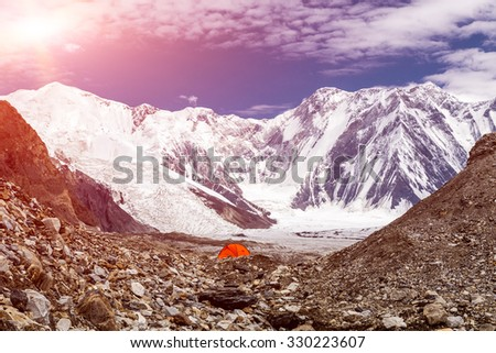 One Red Camping Tent Located on Rock Moraine of Giant Glacier in High Altitude Mountains with Peak Range and Summits on Background Sunny Weather Blue Sky with some Clouds - stock photo
