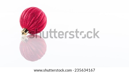 One red Christmas ball isolated on white reflective perspex background with copy space - stock photo