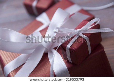 One Red Christmas Gifts, Presents With White Ribbon As Decoration. Shabby Chic, Rustic, Vintage Wooden Background. Copy Space For Advertisement. Card For Birthday Greetings. Close up Or Macro - stock photo