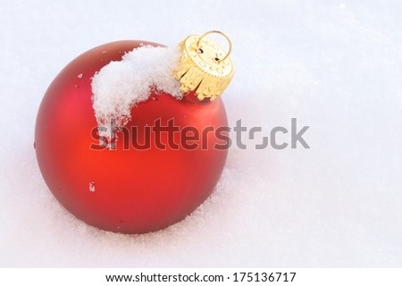 One Red Christmas Ornament Laying in Snow - stock photo