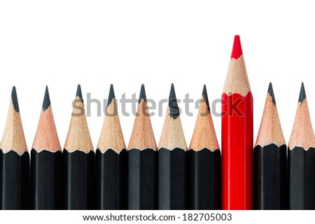 One red pencil standing out from the row of black pencils - stock photo