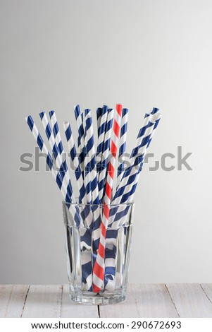 One red striped drinking straw mixed in with a bunch of blue striped straws. The straws are fanned out in a drinking glass on a wood table against a light to dark gray background. - stock photo