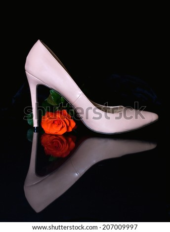 One reflected red rose and one high heeled sexy shoes. - stock photo