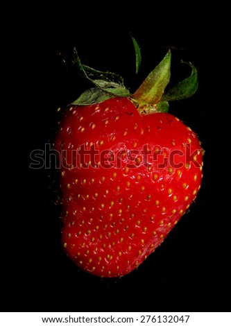 One ripe red strawberry on black - stock photo